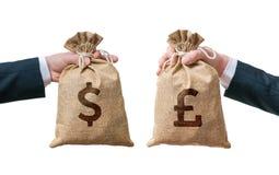 Utbytesvalutabegrepp Händer rymmer påsen full av pengar - dollar och brittiska pund arkivfoton