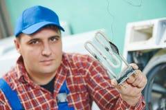 Utbytning av den turbular elektriska uppvärmningbeståndsdelen av tvagningmaskinen Royaltyfri Bild