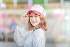 Utdoorportret van het jonge mooie modieuze gelukkige smilngdame stellen op Model die hoed GLB en modieuze kleren dragen Meisjeslo Royalty-vrije Stock Fotografie