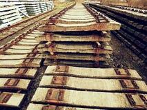 Utdragna gamla konkreta längsgående stödbjälke i materiel Lagrade gamla rostiga använda konkreta järnväg band Fotografering för Bildbyråer
