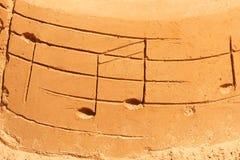 Utdragna musikaliska anmärkningar på sand royaltyfria foton