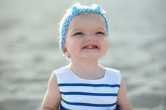 Сute baby girl in nice striped dress and blue headband smiling and showing her first teeth. Close up portrait of a cute baby girl in nice striped dress and blue Stock Images