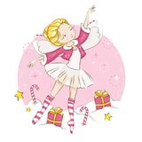 Сute Christmas fairy. Beautiful little fairy. She`s blonde. Princess dancing in a ballerina costume. She is wearing socks with a Christmas pattern  and a red Stock Images