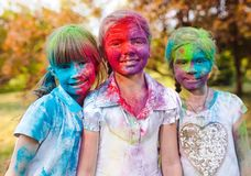 Cute european child girls celebrate Indian holi festival with colorful paint powder on faces and body stock photography