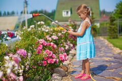 ?ute girl in blue dress watering flowers with a Stock Photography