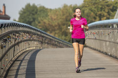 Сute girl while jogging in the city. Healthy lifestyle. Stock Photo