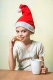 Сute girl in Santa Claus hat eat cookies. Stock Photography
