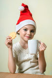 Сute girl in Santa Claus hat eat cookies. Stock Photo