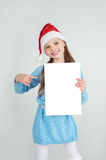 Сute girl in Santa Claus hat with a white blank paper sheet. С Stock Image