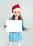 Сute girl in Santa Claus hat with a white blank paper sheet. С Royalty Free Stock Photos
