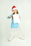 Сute girl in Santa Claus hat with a white blank paper sheet. С Stock Photography