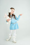 Сute girl in winter clothes pointing to something.  Royalty Free Stock Photos