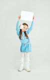 Сute girl in winter clothes with a white blank paper sheet Royalty Free Stock Photo