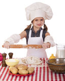 Сute little girl baking on kitchen and shows rolling-pin Stock Images