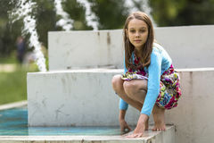 Сute little girl in summer outdoors, near the fountains. Royalty Free Stock Images