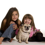 Ute little girls with their pet pug dog. Portrait of two cute little girls with their pet pug dog Royalty Free Stock Photography