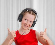 Сute teen girl listening to music in headphones and showing a thumbs up gesture Stock Images