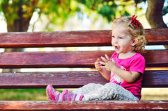 сute toddler on the bench Royalty Free Stock Images