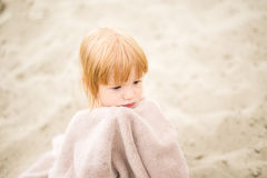Сute toddler girl with red hair wrapped in towel at the beach Royalty Free Stock Images