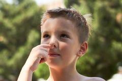 Ute weinig jongen die plukkend zijn neus, close-up genieten van stock foto