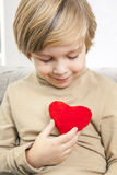 Сute young boy with a red heart. Cute young boy with a red heart in his hands Stock Image