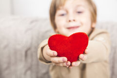 Сute young boy with a red heart. Cute young boy with a red heart in his hands Royalty Free Stock Image
