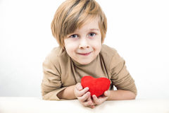 Сute young boy with a red heart Royalty Free Stock Images