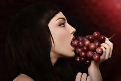 Uteflicka med röda druvor Arkivfoto