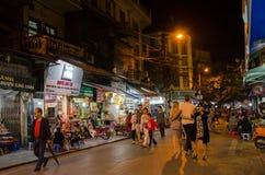 Uteliv av gatasikten i Hanoi den gamla fjärdedelen, folk kan sedd undersökning och att shoppa runt om det Fotografering för Bildbyråer