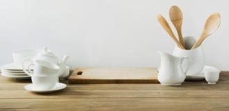 Utensílios brancos da cozinha, dishware e o outro material branco diferente para servir na placa de madeira branca fotografia de stock royalty free