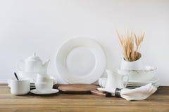 Utensílios brancos da cozinha, dishware e o outro material branco diferente para servir na placa de madeira branca fotos de stock royalty free