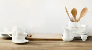 Utensílios brancos da cozinha, dishware e o outro material branco diferente para servir na placa de madeira branca imagem de stock royalty free