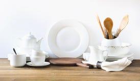 Utensílios brancos da cozinha, dishware e o outro material branco diferente para servir na placa de madeira branca imagem de stock