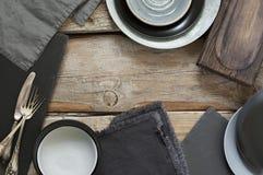 Utensílios cinzentos da cozinha na tabela de madeira afligida áspera Foto de Stock