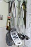 Utensílios da cozinha que penduram na cozinha Foto de Stock