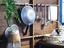 Utensílios da cozinha que penduram sobre a parede de madeira Foto de Stock