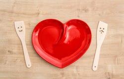 Utensílios de madeira da cozinha e toalha de mesa vermelha Ferramentas engraçadas Imagens de Stock