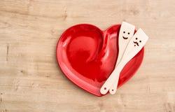 Utensílios de madeira da cozinha na placa vermelha da lareira Alimento engraçado Foto de Stock
