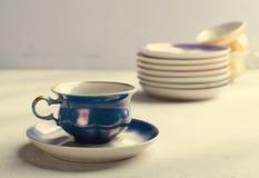 Utensílios de mesa coloridos vazios da porcelana Copo azul com a placa no fundo lilás imagens de stock