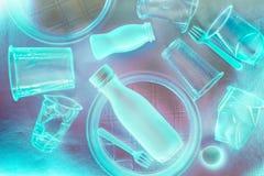 Utensílios de mesa descartáveis plásticos na iluminação de néon azul Conceito da polui??o ambiental imagem de stock