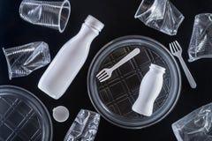 Utensílios de mesa descartáveis plásticos no fundo preto Conceito da polui??o ambiental fotografia de stock
