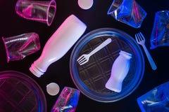Utensílios de mesa transparentes plásticos na iluminação de néon no fundo preto Conceito da polui??o ambiental imagens de stock royalty free