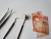 utensílios do dentista para a revisão oral e uma cédula filipino de 20 pesos fotos de stock