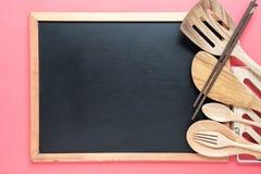 Utensílios retros da cozinha com o quadro-negro vazio no fundo cor-de-rosa fotografia de stock