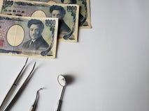 utens?lios do dentista para a revis?o oral e c?dulas japonesas imagens de stock