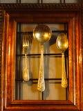 Utensile brillante su un fondo della parete Cucchiai d'argento e poco per Immagine Stock