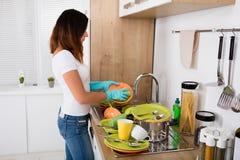 Utensile infelice di lavaggio della donna nella cucina immagini stock libere da diritti