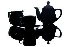 Utensili bianchi del tè nella tonalità su un fondo bianco Immagini Stock