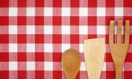 Utensili da cucina su una tovaglia rossa Immagini Stock
