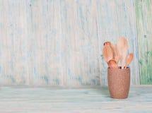 Utensili della cucina, cucchiai di legno in tazze da caffè su legno Immagini Stock